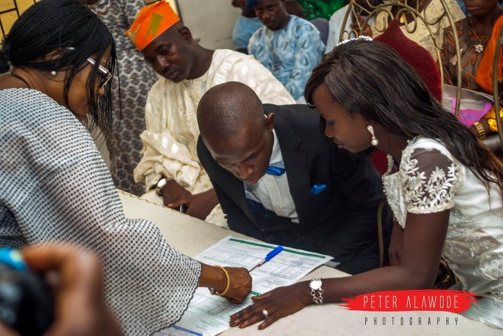 The new couple sign their marriage certificate